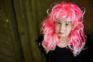 Halloween girl with pink hair and painted long eyelashes looking at camera with confusion