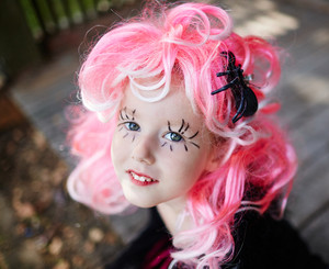 Halloween girl with pink hair and painted long eyelashes looking at camera