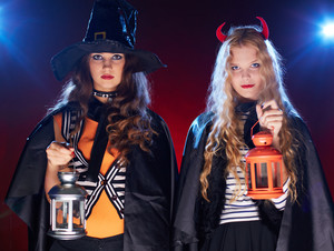 Halloween girls with lanterns looking at camera in the dark
