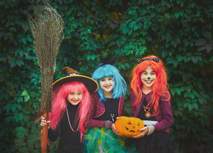 Halloween witches with pumpkin and broom looking at camera on background of green foliage