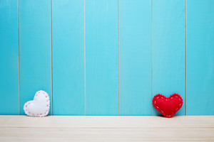 Hand crafted red and white felt hearts on blue wood background