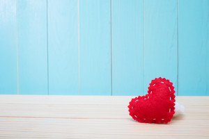 Hand crafted red felt heart on blue wood background