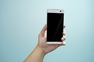Hand holding mobile smart phone with blank screen. Isolated on light blue background.