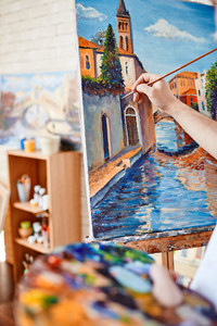 Hand of artist painting street of Venice on canvas