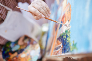 Hand of artist with paintbrush painting on canvas