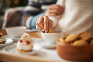 Hand of female with biscuit during tea time in cafe