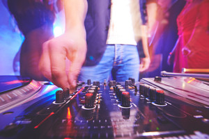Hand of male dj adjusting sound during disco party