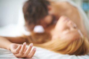 Hand of pleased and relaxed female lying on bed while man caressing her