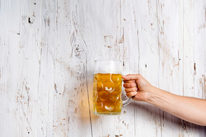 Hand of unrecognizable man holding a beer mug. Oktoberfest. Studio shot on white wooden background. Copy space.