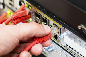 Hand Plugging Network Cable Into Switch In Datacenter
