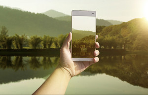 Hand taking photo of the lake and mountain landscape by smartphone