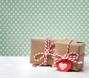 Handmade gift boxes with heart tag on polka dots background