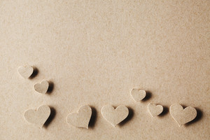 Handmade paper cut hearts on earthy colored paper background