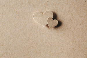 Handmade paper cut hearts on erthy colored paper background