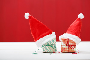 Handmade small gift boxes with Santa hats on red wooden wall