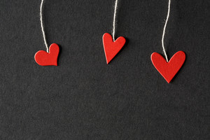 Handmade small paper hearts with strings on black paper background