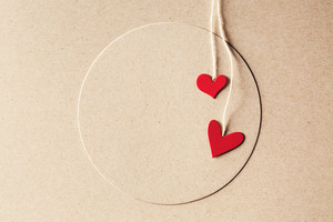 Handmade small paper hearts with strings on earthy colored paper background