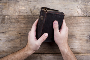 Hands holding Bible on a wooden desk background.