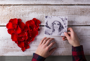Hands of a man holding photo of his girlfriend. Red rose petal heart. Valentines day composition.