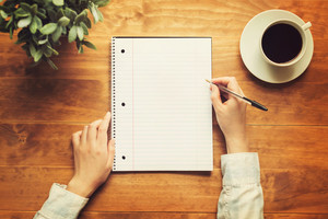 Hands of a person writing in a small notepad on a wooden desk