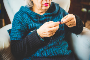 Hands of a woman knitting with knitting needles and woolen yarn, filtered vintage - handcraft, hobby concept