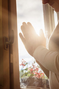 Hands of an unrecognizable woman standing by the window and praying