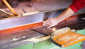 Hands of carpenter working with electric wood planer in his workshop