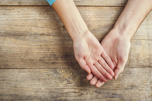 Hands of man and woman holding together. Studio shot on a wooden background, view from above.