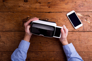 Hands of man holding virtual reality goggles and smart phone. Flat lay. Studio shot on wooden background.