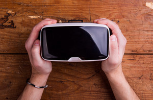 Hands of man holding virtual reality goggles. Flat lay. Studio shot on wooden background.