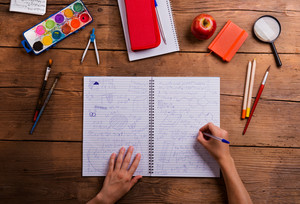 Hands of man writing into the notebook with math symbols and formulas. Various school supplies, flat lay. Studio shot on wooden background.
