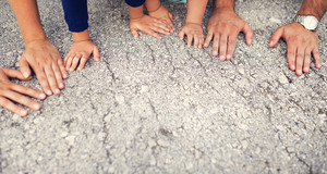 Hands of parents with their kids laid on the ground