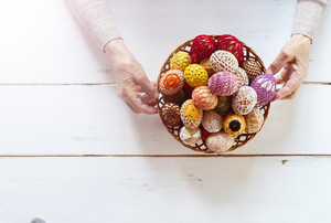 Hands of senior woman with basket full of easter eggs on a wooden white background.