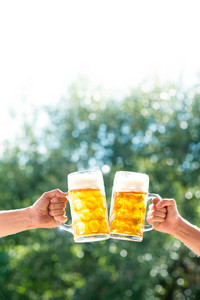 Hands of two unrecognizable men holding mugs of beer, clinking. Oktoberfest. Sunny summer garden.