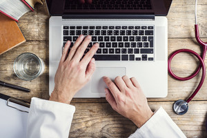 Hands of unrecognizable doctor writing on a computer. Wooden desk background.