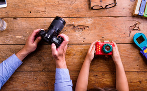 Hands of unrecognizable father and son holding cameras, old office desk. Studio shot on wooden background. Flat lay.