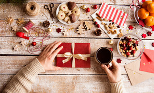 Hands of unrecognizable man holding Christmas present and cup of coffee. Various objects laid on a wooden table background.