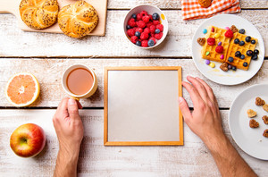 Hands of unrecognizable man holding empty picture frame. Breakfast meal. Studio shot on white wooden background. Flat lay, copy space.