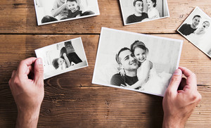 Hands of unrecognizable man holding pictures of young father and his cute little daughter. Fathers day concept. Studio shot on woden background.