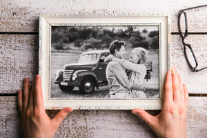 Hands of unrecognizable man looking at black-and-white photo of senior couple in white picture frame. Studio shot on white wooden background.