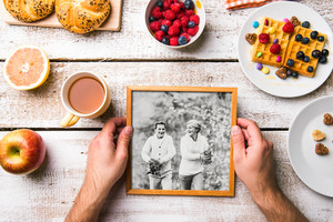 Hands of unrecognizable man looking at black and white picture of senior couple in autumn nature. Breakfast meal laid on table. Studio shot on white wooden background.