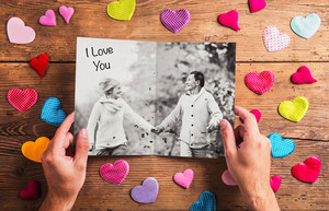 Hands of unrecognizable man looking at black and white picture of senior couple with I love you sign, colorful fabric hearts surrounding it. Studio shot on wooden background.