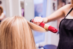 Hands of unrecognizable professional hairdresser creating hairstyle for her beautiful blond client. Straightening iron, blonde female customer.