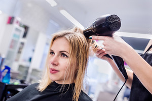Hands of unrecognizable professional hairdresser drying hair of her client, new haircut, blonde female customer.