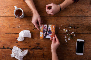 Hands of unrecognizable sad man and woman holding torn picture of couple in love. Ended relationship. Crying.Valentines day composition. Studio shot on brown wooden background.