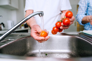 Hands of unrecognizable senior man in white t-shirt washing tomatoes under the tap. Preparing breakfast.