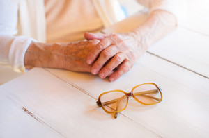 Hands of unrecognizable senior woman holding glasses