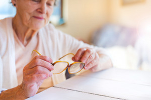 Hands of unrecognizable senior woman holding glasses