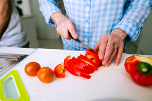 Hands of unrecognizable senior woman in checked blue shirt cutting red peppers. Preparing breakfast.