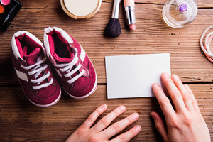 Hands of unrecognizable woman holding empty paper note. Little childrens shoes and various make up products. Studio shot on wooden background. Flat lay, copy space.
